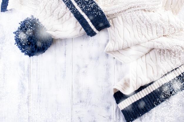 Gestrickter winterschal und eine weiße kappe mit einem blauen streifen auf einem weißen hölzernen hintergrund