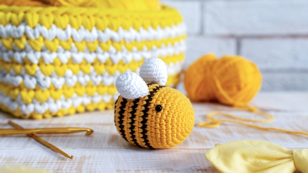 Gestricktes gelbes bienenspielzeug mit strickausrüstung auf dem tisch