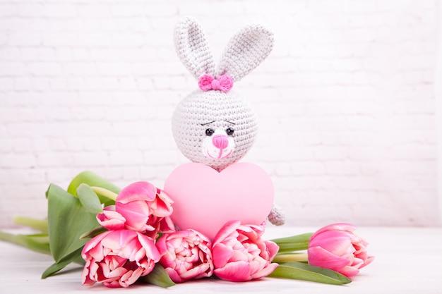 Gestricktes kaninchen. festliche einrichtung. zarte rosa tulpen. valentinstag. handgemachtes, gestricktes spielzeug, amigurumi