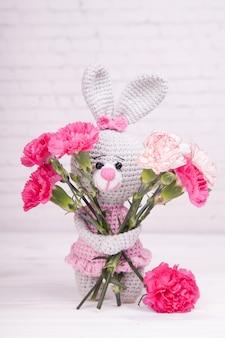 Gestricktes kaninchen festliches dekor. blumenstrauß aus nelken valentinstag. handgemachtes, gestricktes spielzeug, amigurumi
