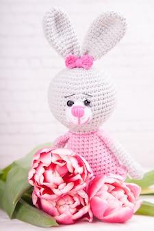 Gestricktes kaninchen festliches dekor. zarte rosa tulpen. valentinstag. handgemachtes, gestricktes spielzeug, amigurumi