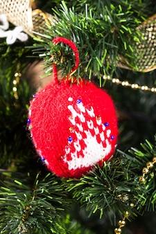Gestricktes spielzeug am weihnachtsbaum, nahaufnahme