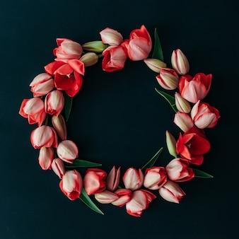 Gestyltes minimalistisches stillleben mit tulpenblumen auf dunklem hintergrund. flach liegen.