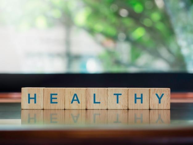 Gesund, wörter auf hölzernen würfelblöcken auf braunem hölzernem schreibtischhintergrund. gesundheitsversorgung, wohlbefinden und medizinisches konzept.