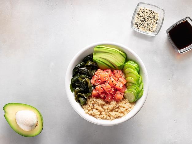 Gesunde abendessen-buddha-schüssel mit quinoa-lachs-wakame-algen-avocado-traditionelles asiatisches essen