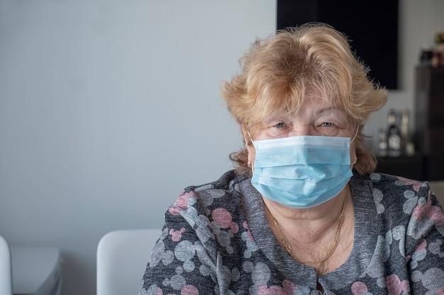 Gesunde ältere frau in der blauen medizinischen schutzmaske bleiben zu hause. coronavirus-ausbruch. speicherplatz kopieren