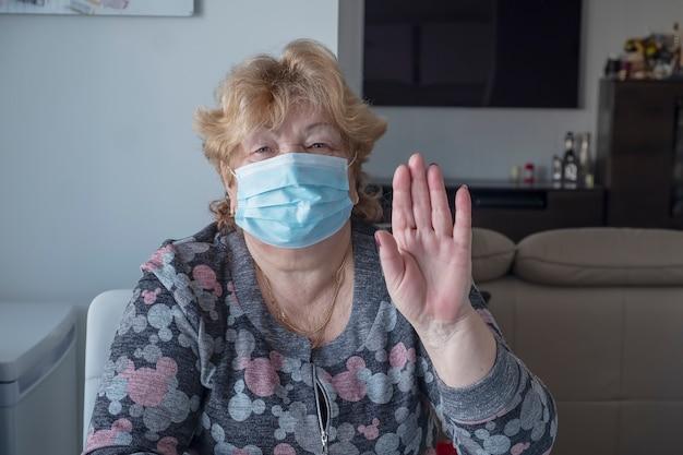 Gesunde ältere frau in der blauen medizinischen schutzmaske, die gestenstopp zeigt. coronavirus-ausbruch