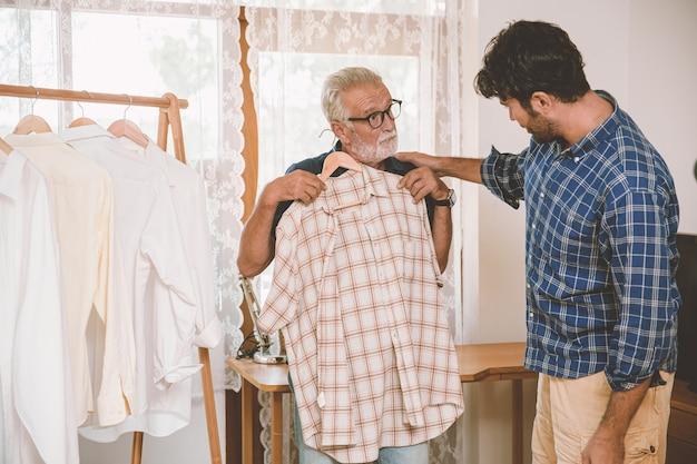 Gesunde ältere menschen, die kleidung für die reise auswählen, hängen mit sohn und familie im urlaub zusammen.