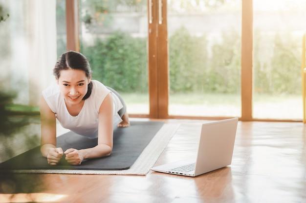 Gesunde asiatische frau, die plankenübung zu hause in einem wohnzimmer tut, während online-trainingseinheit vom laptop beobachtet.