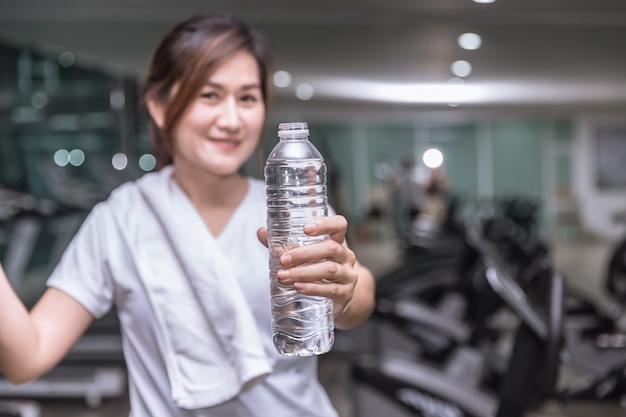 Gesunde asiatische frauenhandgriffshowflasche getränkwasser mit sportvereinhintergrund