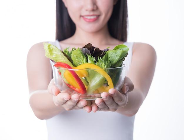 Gesunde asien-frau mit dem salat lokalisiert auf weißem hintergrund