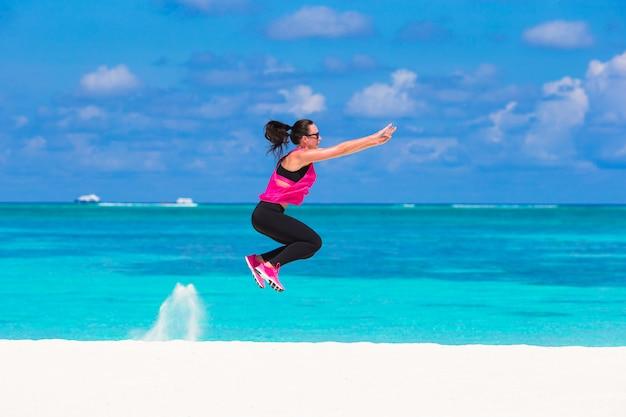Gesunde athletenfrau, die übung auf tropischem weißem strand tuend ausarbeitet