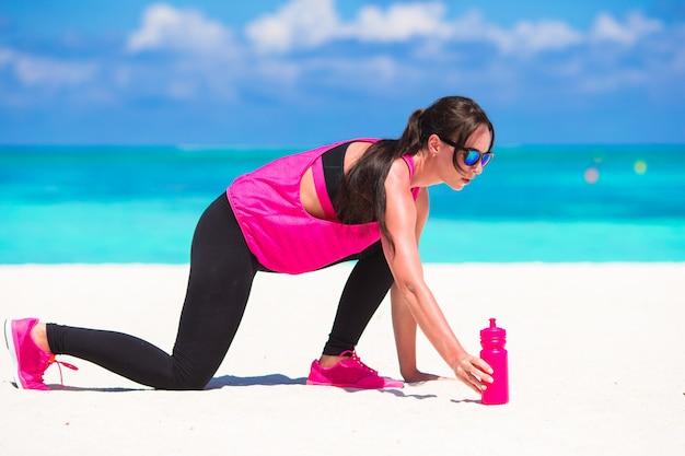 Gesunde athletenfrau, die übung auf weißem strand tuend ausarbeitet