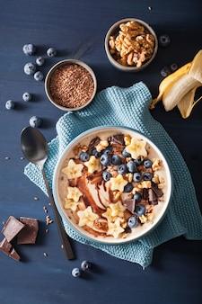 Gesunde bananen-smoothie-schüssel mit heidelbeer-schokoladen-walnüssen