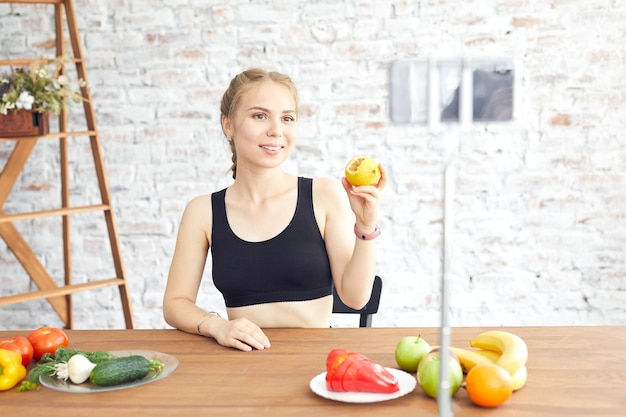 Gesunde bloggerin der frau zeigt apfelfrucht und sauberes diätfutter. vlogger aufzeichnung von vlog-video-live-streaming zu hause. zeugen des vlog-konzepts.