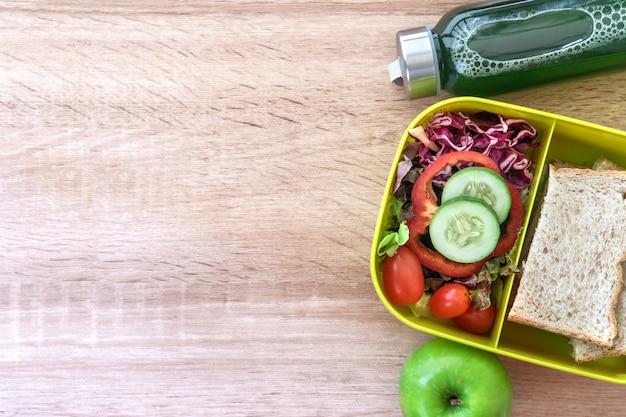 Gesunde brotdose mit kornbrot und grüner gemüse- und fruchtsaftflasche