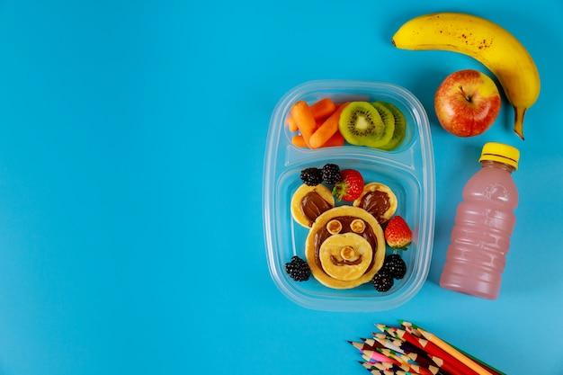 Gesunde brotdose mit pfannkuchen und haselnussaufstrich, obst und gemüse.