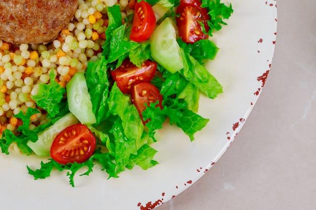 Gesunde couscouspasteten mit salat, schweinekoteletts