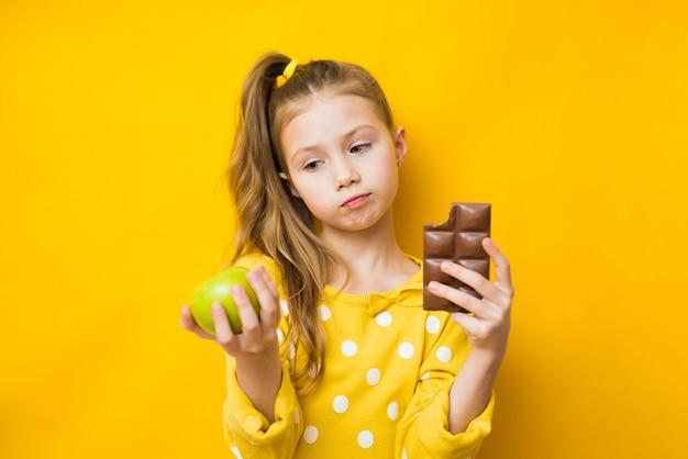 Gesunde diät entscheidungen - kleines mädchen mit apfel und schokolade auf gelbem hintergrund