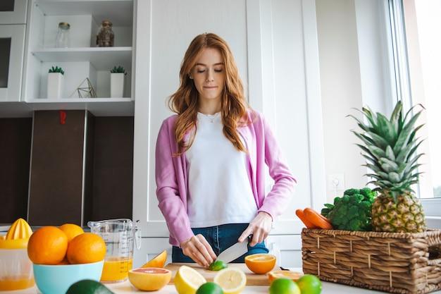 Gesunde diätfrau, die früchte für frisches natürliches getränk des saftes schneidet