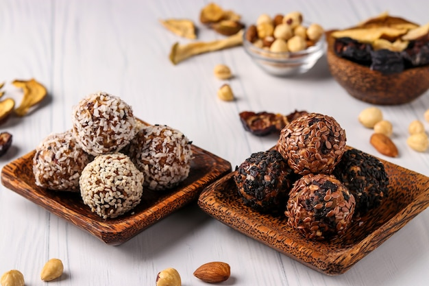 Gesunde energiekugeln aus nüssen, haferflocken und getrockneten früchten mit kokos-, leinsamen- und sesamkörnern auf hölzernen kokosnusstellern auf einer weißen oberfläche, horizontale ausrichtung, nahaufnahme