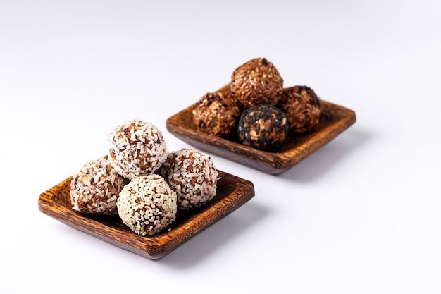 Gesunde energiekugeln aus nüssen, haferflocken und trockenfrüchten mit kokos-, leinsamen- und sesamkörnern auf hölzernen kokosnusstellern auf weißer oberfläche, horizontale ausrichtung, kopierraum