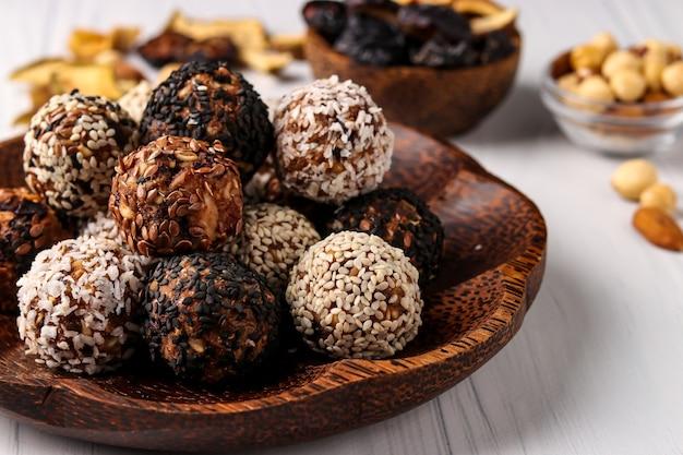 Gesunde energiekugeln aus nüssen, haferflocken und trockenfrüchten mit kokosnuss-, leinsamen- und sesamkörnern auf kokosnuss