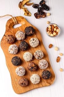 Gesunde energiekugeln von nüssen, haferflocken und getrockneten früchten mit kokosnuss-, leinsamen- und sesamkörnern auf holzbrett auf einer weißen oberfläche, vertikale ausrichtung, draufsicht, nahaufnahme