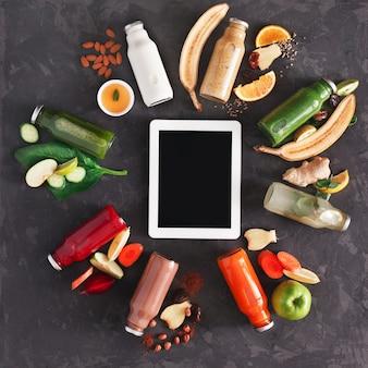 Gesunde entgiftungsgetränke mit obst- und gemüsezutaten und tablette. glasflaschen mit smoothie, draufsicht, flach liegen. internet online bestellen konzept