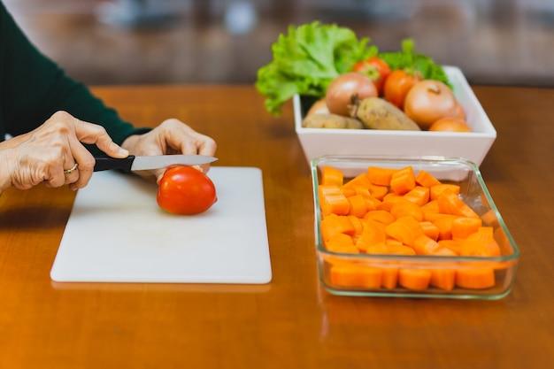 Gesunde ernährung, ältere frau, die tomate zum kochen hackt.