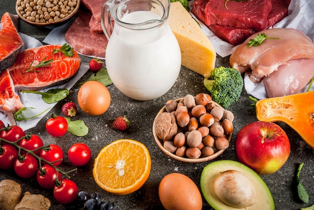 Gesunde ernährung . bio-lebensmittelzutaten, superfoods: rind- und schweinefleisch, hühnerfilet, lachsfisch, bohnen, nüsse, milch, eier, obst, gemüse. schwarzer steintisch, copyspace
