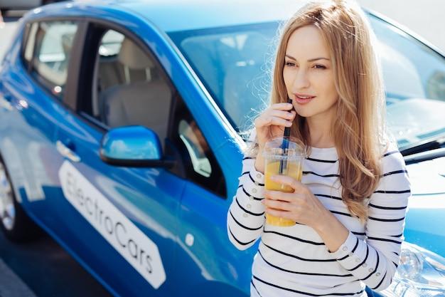 Gesunde ernährung. freudige nette positive frau, die eine tasse hält und orangensaft trinkt, während sie einen strohhalm hält