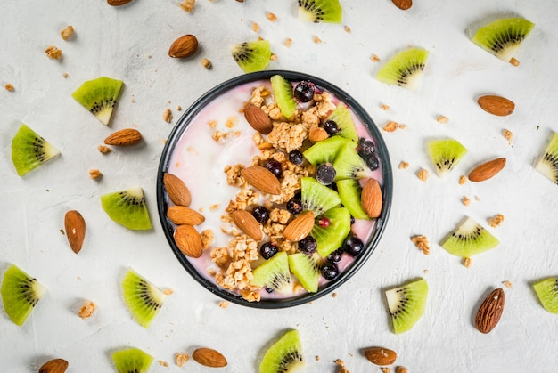 Gesunde ernährung frühstück: smoothies schüssel, mit joghurt, frischen heidelbeeren (schwarze johannisbeere), kiwi, müsli haferflocken, mandeln. auf einem weißen steintisch, mit einem glas wasser und zutaten. ansicht von oben