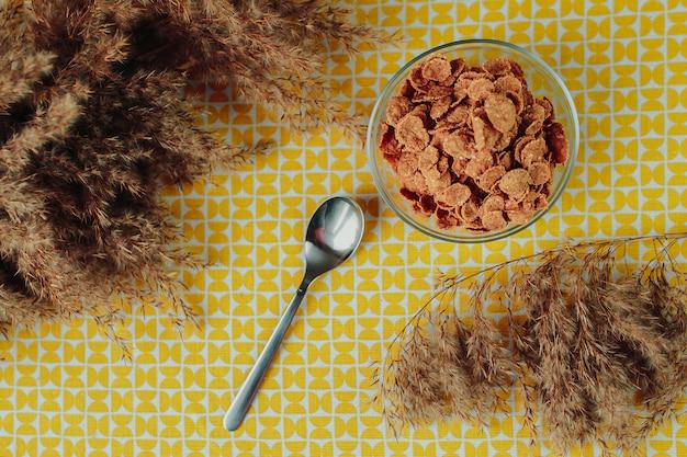 Gesunde ernährung, gesundes essen auf dem tisch, dunkles müsli in der glasschale, löffel und getrocknete blumen herum.