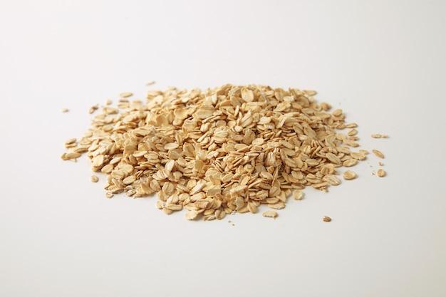 Gesunde ernährung haferflocken isoliert auf weiß in der mitte, vorbereitet für das kochen von müsli zum frühstück