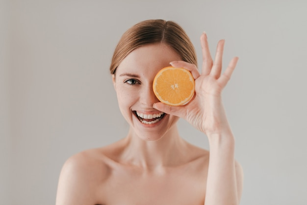 Gesunde ernährung macht schön. attraktive junge frau mit sommersprossen im gesicht, die orangenscheibe hält und lächelt, während sie vor dem hintergrund steht