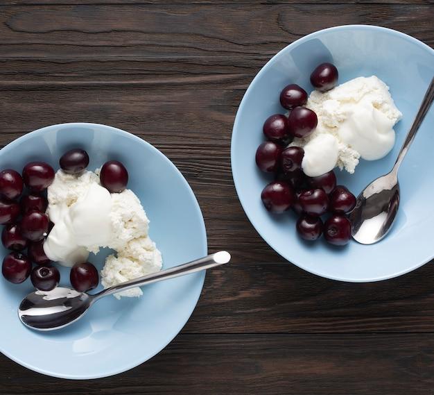 Gesunde ernährung reife kirschen mit hüttenkäse. dessert, snack, diät