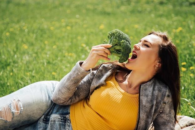 Gesunde ernährung. schöne frau, die frischen organischen brokkoli isst. gesunde lebensmittel, vegetarische ernährung und gesundheitskonzept