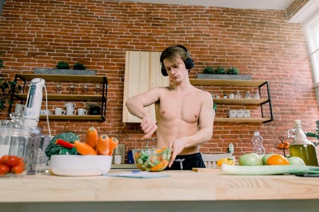 Gesunde ernährung und nahrungsergänzungsmittel. hübscher mann, der musik hört und tanzt, während er einen salat bereitet, der sportgetränk in der küche genießt. bodybuilding-konzept