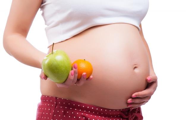 Gesunde ernährung und schwangerschaft. bauch der schwangeren frau und gesundes essen