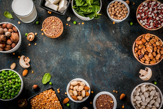 Gesunde ernährung veganes essen, vegetarische proteinquellen: tofu, vegane milch, bohnen, linsen, nüsse, sojamilch, spinat und samen. draufsicht über weiße tabelle.