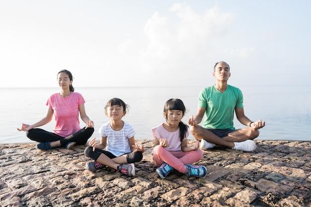 Gesunde familie meditieren gemeinsam im freien
