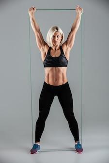 Gesunde fitnessfrau mit erhobenen armen, die sich mit elastischem gummi dehnen