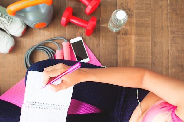 Gesunde frau der draufsicht, die zu hause tägliches training, diät- und eignungskonzept plant