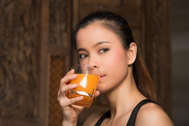 Gesunde frau, die ein glas orangensaft trinkt