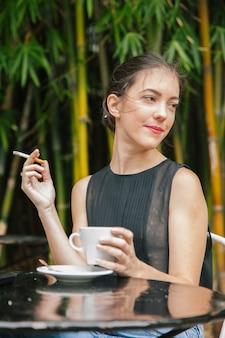 Gesunde frau, die einen kaffee und eine zigarette hat