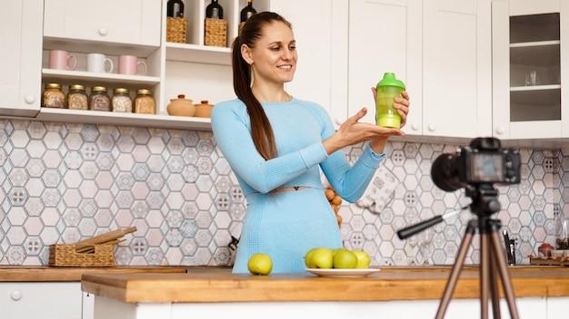 Gesunde frau, die ihren videoblog über gesunde lebensmittelzusatzstoffe aufzeichnet, während sie in der küche steht. sie hält eine flasche sporternährung in der hand und lächelt