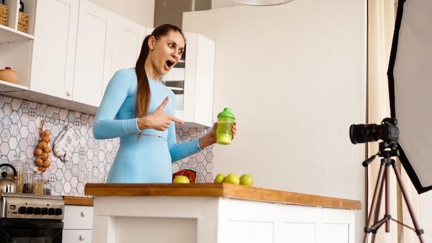 Gesunde frau, die ihren videoblog über gesunde lebensmittelzusatzstoffe aufzeichnet, während sie in der küche steht. sie hält eine flasche sportnahrung und lächelt