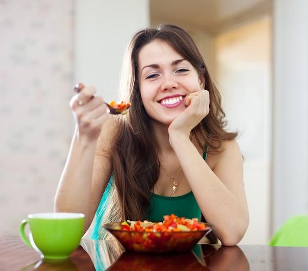 Gesunde frau, die veggiesalat isst