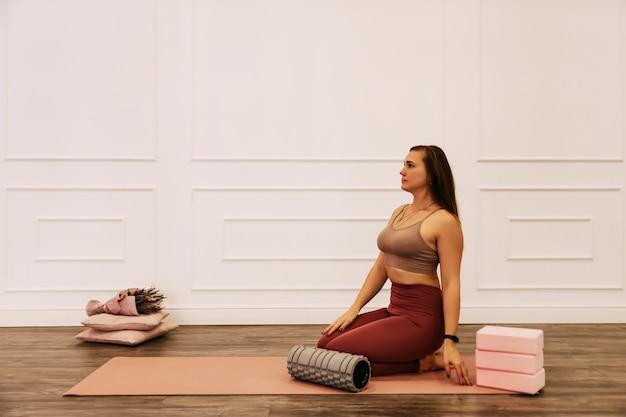 Gesunde frau fitnessmatte, die aufwärmübung tut. fit frau sitzt auf trainingsmatte dehnung